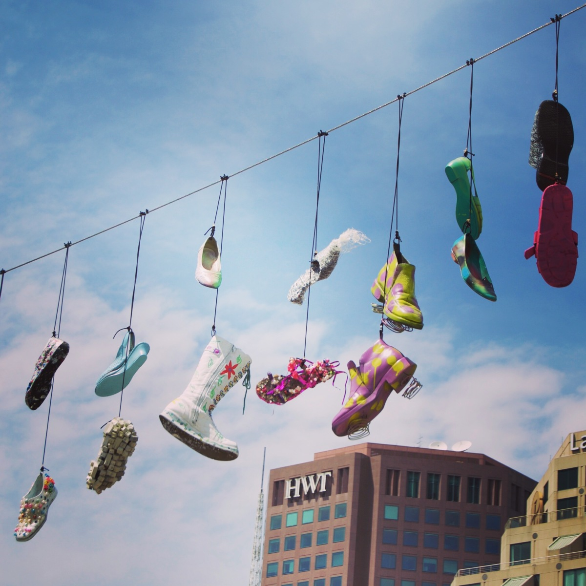 Shoes dangling against a blue sky